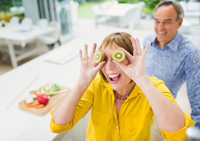 Mature woman covering eyes with kiwi slices