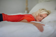Serene woman sleeping on bed with eyes closed