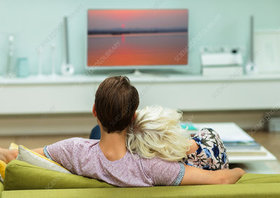 Relaxed couple watching TV on living room sofa