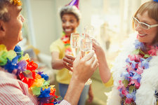 Mature friends in feather boas and leis toasting