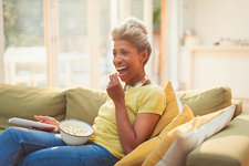 Mature woman eating popcorn and watching TV