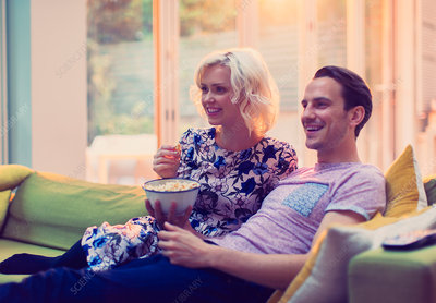 Couple watching TV and eating popcorn on sofa