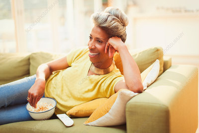 Mature woman watching TV and eating popcorn
