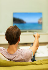 Man watching TV changing channels on sofa