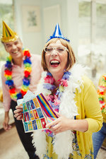 Mature woman in party hat holding birthday gift