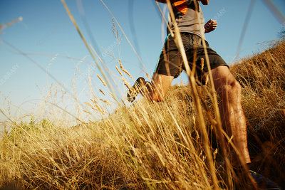 Man running through tall grass on sunny trail
