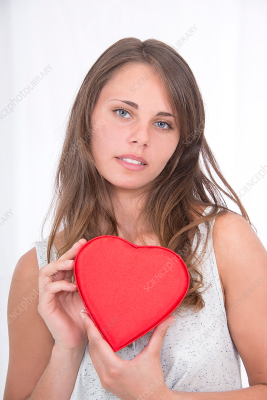 Young woman holding red heart shape