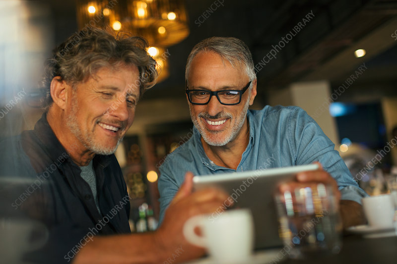 Men using digital tablet at restaurant table