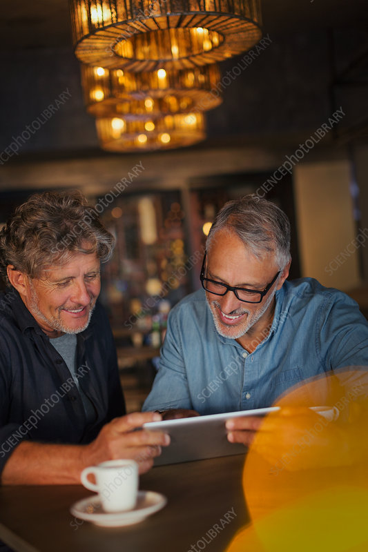 Men using digital tablet and drinking coffee