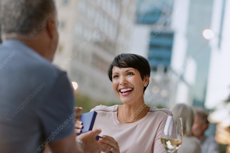 Smiling woman receiving gift from husband