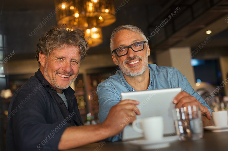 Portrait smiling men using digital tablet