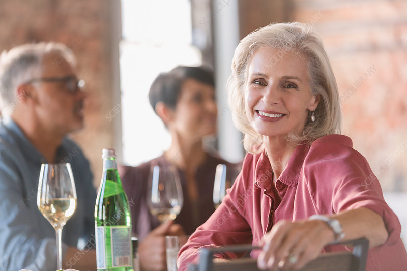 Portrait smiling senior woman dining with friends