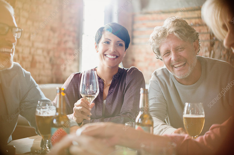 Laughing couples drinking white wine and beer