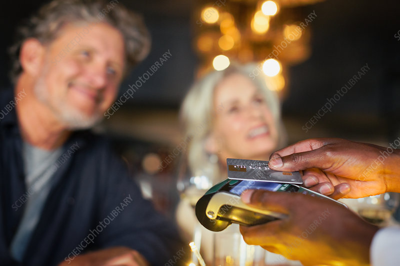 Couple paying waiter with credit card