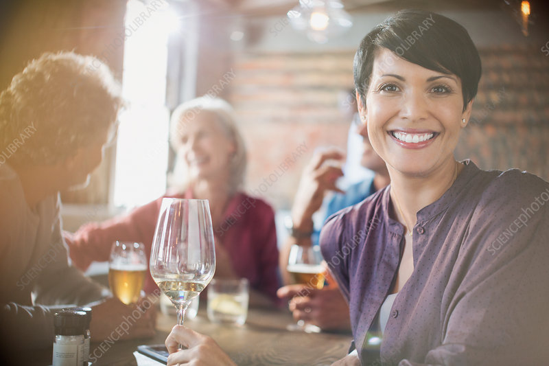 Woman drinking white wine dining with friends