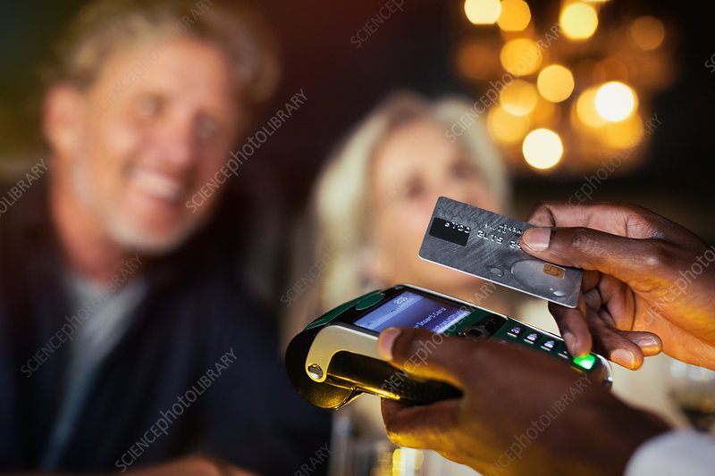 Close up couple paying waiter with credit card