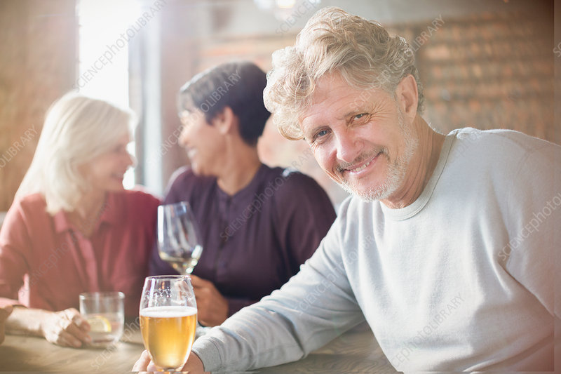 Senior man drinking beer dining with friends