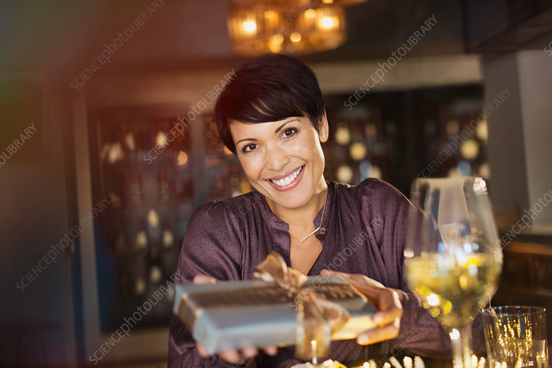 Portrait smiling woman giving gift in bar