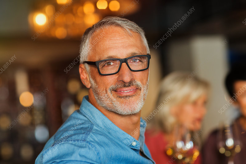 Portrait confident man with eyeglasses at bar