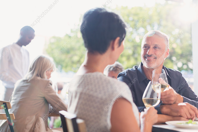 Couple talking and drinking white wine