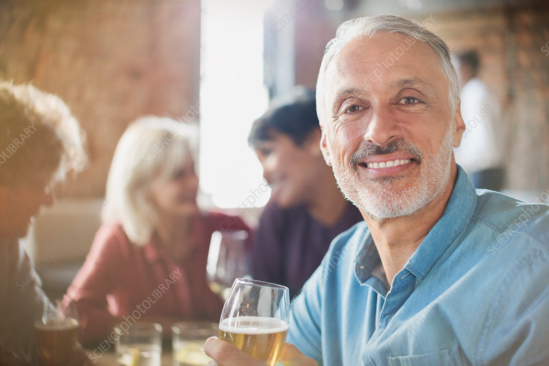 Portrait man drinking white wine with friends