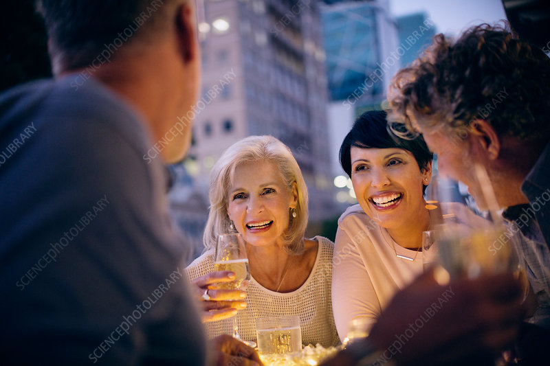 Smiling couples drinking white wine and talking