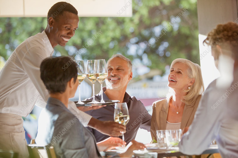 Waiter serving white wine to couples