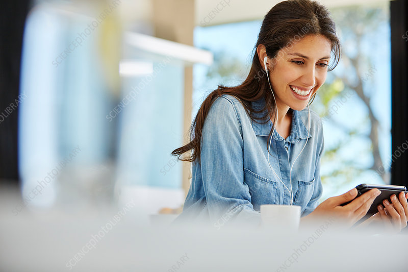 Smiling woman using digital tablet and headphones