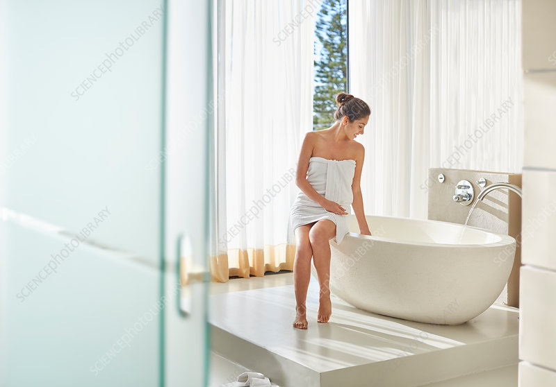 Woman wrapped in towel preparing a bath