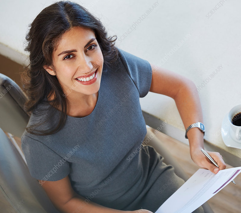 Portrait smiling businesswoman reviewing paperwork
