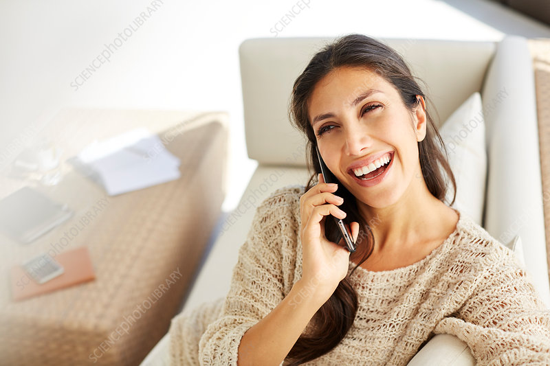 Laughing woman talking on cell phone on sofa