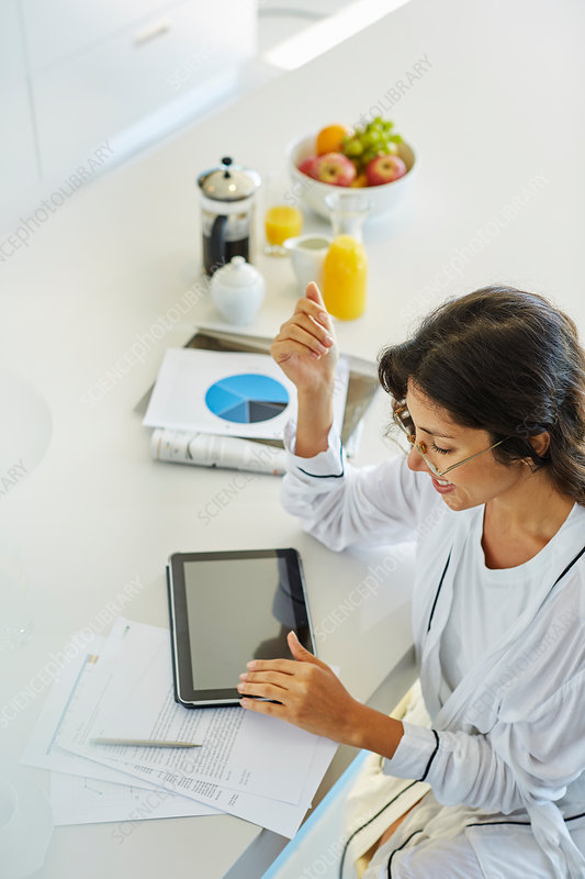 Woman working at digital tablet at kitchen counter