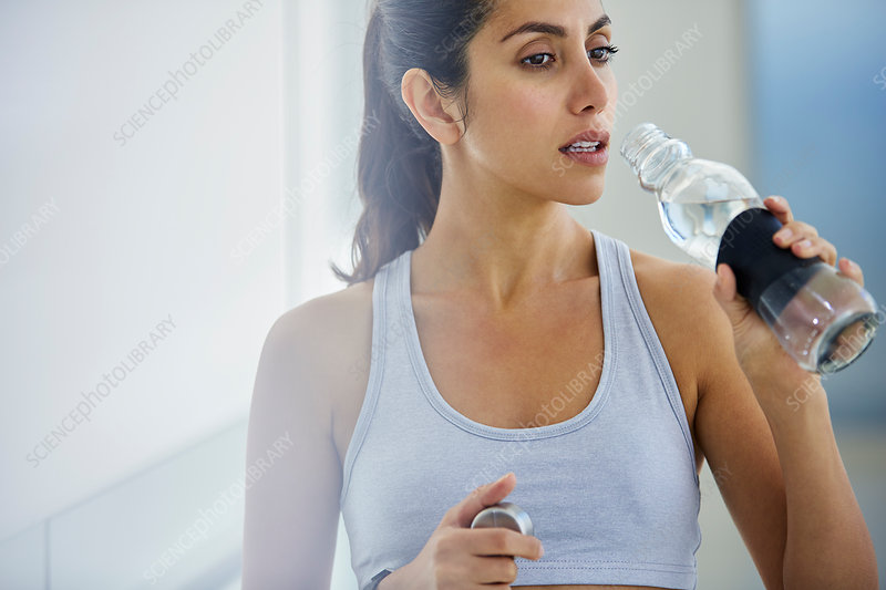 Woman drinking water post workout