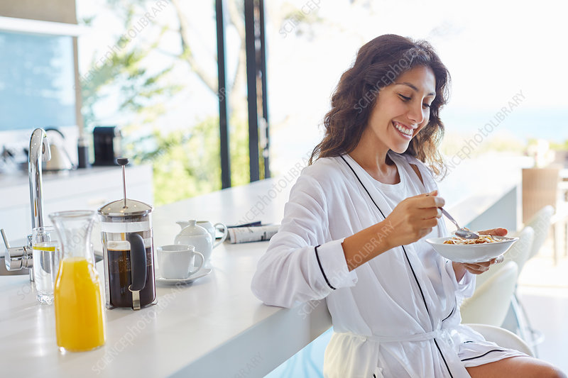Smiling woman in bathrobe eating cereal
