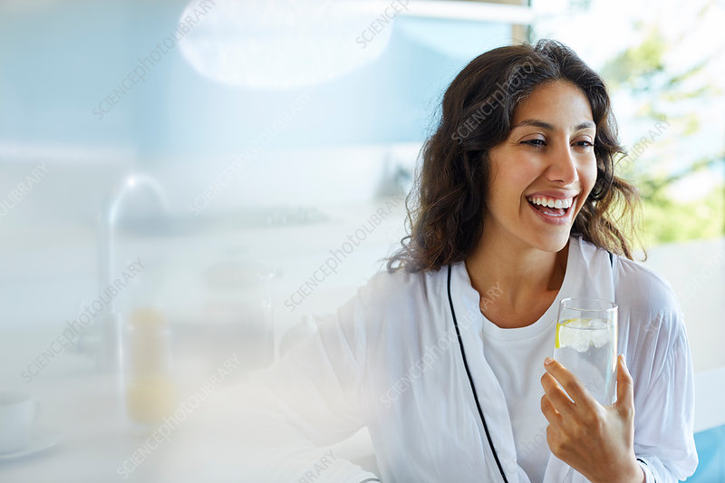 Laughing woman in bathrobe drinking water