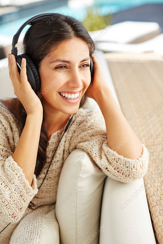 Smiling woman listening to music on sofa