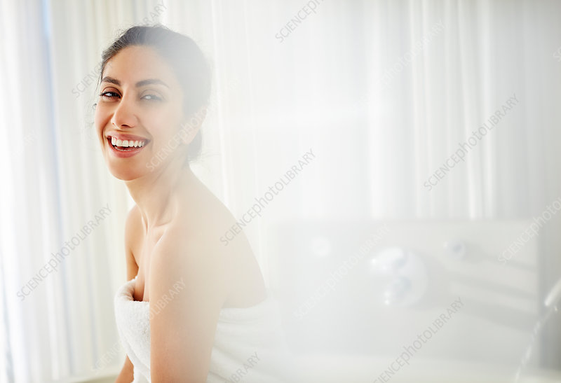 Portrait smiling woman wrapped in towel