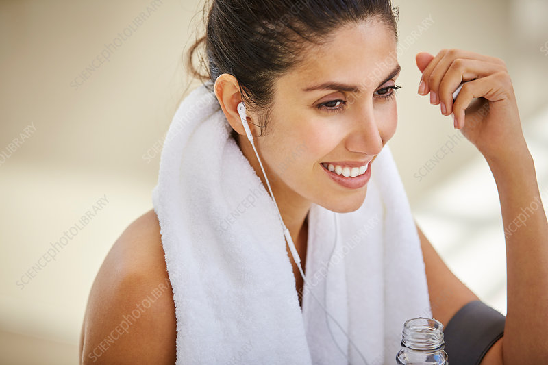 Woman with towel listening to music post workout