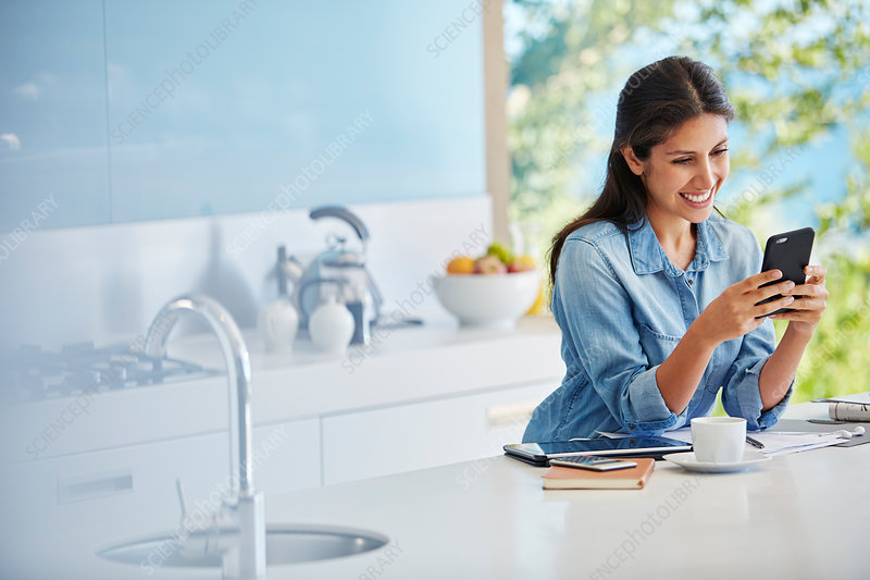 Woman texting with cell phone at kitchen counter