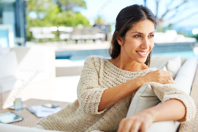 Smiling woman looking away on patio sofa