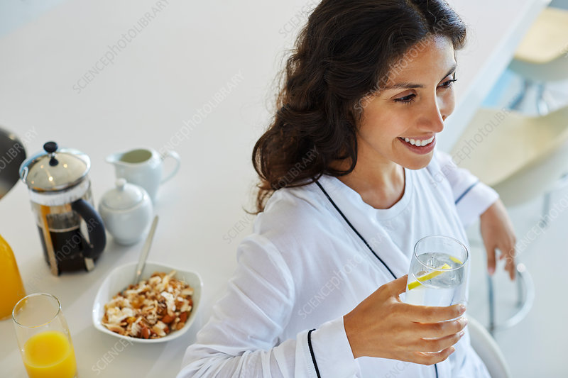 Smiling woman in bathrobe drinking water