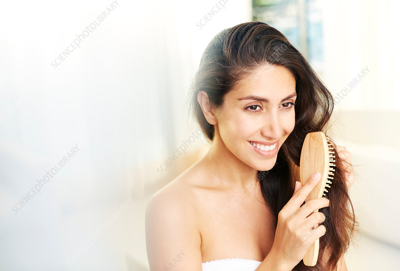 Smiling brunette woman brushing hair