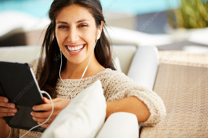 Woman using digital tablet and headphones on sofa
