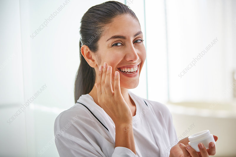 Portrait smiling woman apply face cream to cheek