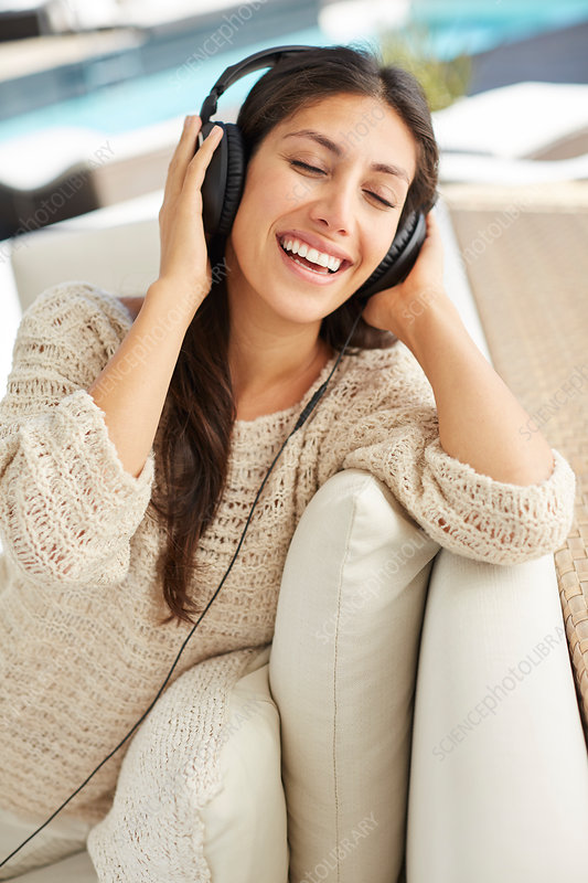 Carefree woman listening to music on sofa