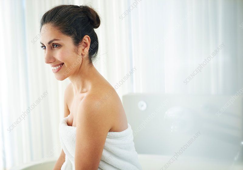 brunette woman wrapped in towel looking away