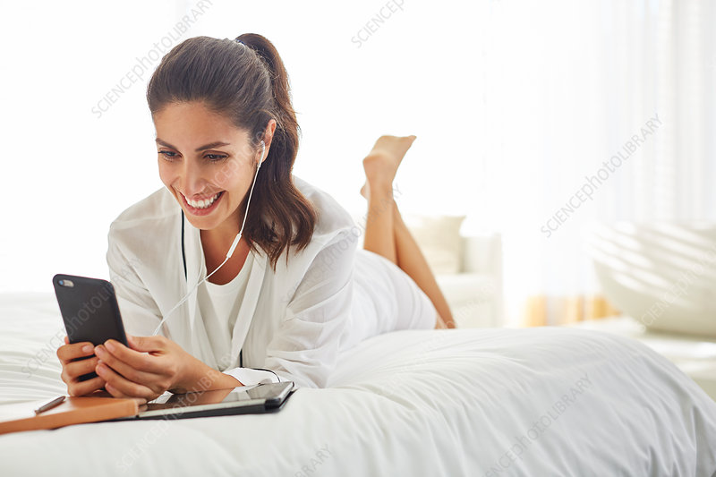 Woman listening to music and mp3 player on bed