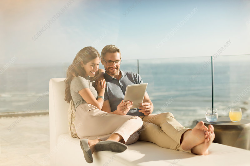 Couple relaxing using digital tablet