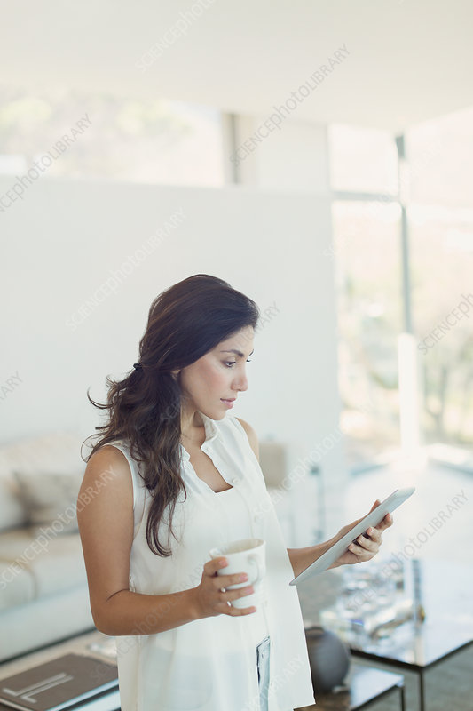 Serious woman drinking coffee using digital tablet