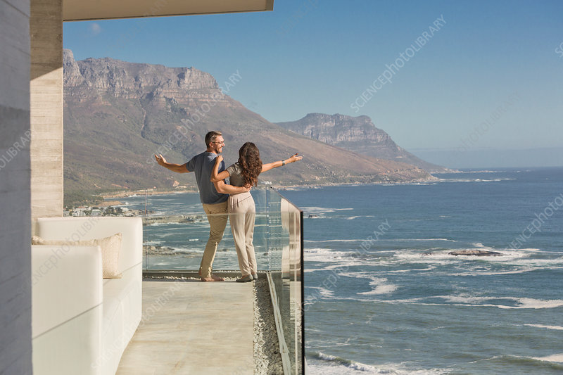 Carefree couple standing on sunny luxury balcony